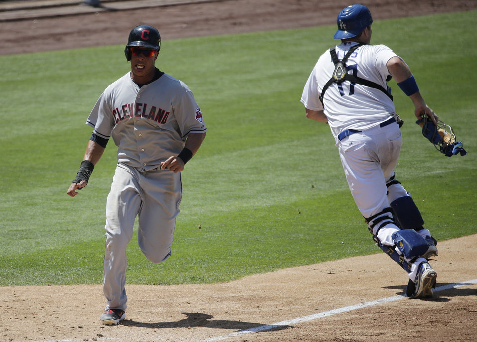 Photo - Cleveland Indians' Michael Brantley, left, runs toward home plate to score on a single hit by David Murphy as Los Angeles Dodgers catcher A.J. Ellis, right, goes after the throw during the eighth inning of a baseball game on Wednesday, July 2, 2014, in Los Angeles. (AP Photo/Jae C. Hong)