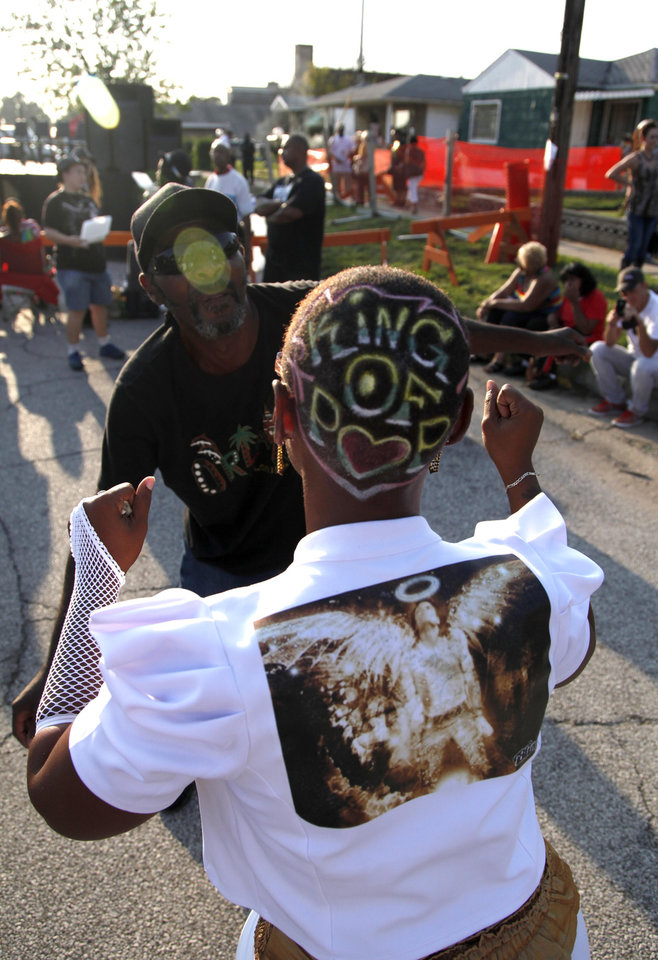 Photo -   Angela Burnham and Lawrence Quarles dance to recorded music outside Jackson's boyhood home during celebrations marking what would have been Jackson's 54th birthday Wednesday, Aug. 29, 2012, in Gary, Ind. (AP Photo/Charles Rex Arbogast)