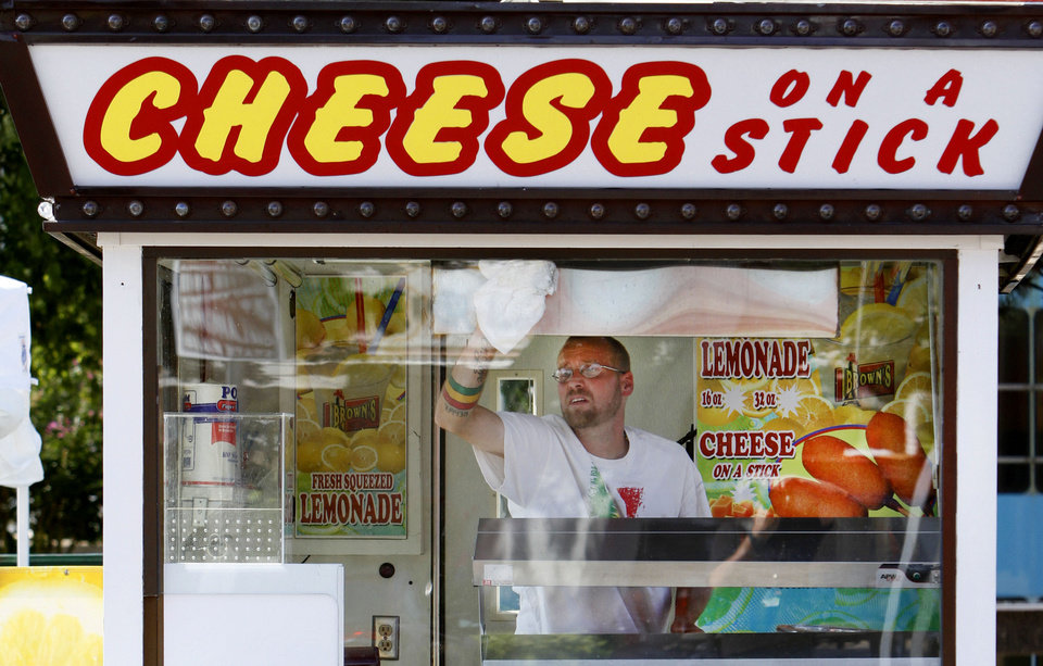 Photo - Sammy Clifton cleans the glass on a Brown's Cheese on a Stick booth Wwednesday at State Fair Park in Oklahoma City. The Oklahoma State Fair starts Thursday. Photo By Steve Gooch, The Oklahoman  Steve Gooch - The Oklahoman