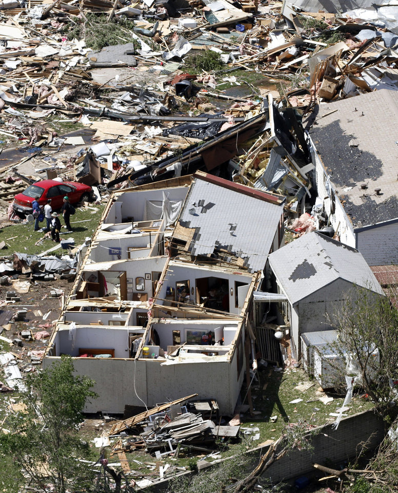 Photo -   RE-TRANS FOR IMPROVED TONING - People examine the damage in the Oaklawn neighborhood in Wichita, Kan., on Sunday, April 15, 2012, caused by one of several tornadoes that hit the state on Saturday. (AP Photo/Jeff Tuttle)