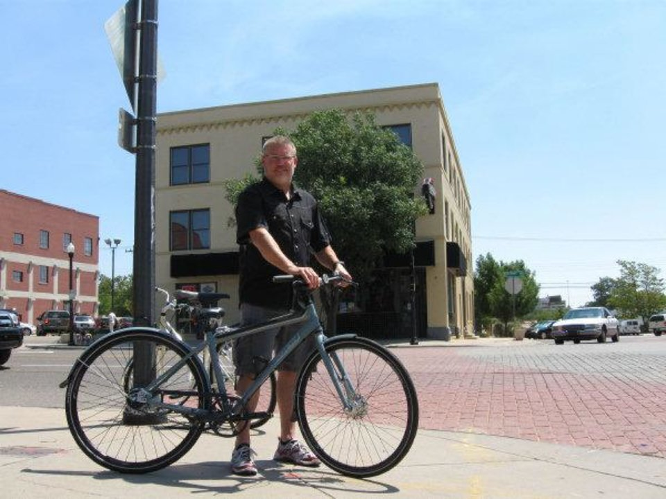 Photo - Steve Schlegel, owner of Schlegel Bicycles, displays a typical commuting bicycle similar to those that will be used as part of a downtown bike share program. Behind Schlegel is a bicycle chained to a lamppost by a worker inside a nearby Hideaway Pizza restaurant.  Steve Lackmeyer