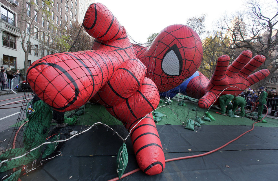 Photo -   Workers inflate the Spider-Man balloon for the 86th annual Macy's Thanksgiving Day Parade, on New York's Upper West Side, Wednesday, Nov. 21, 2012. More than 3 million people typically attend the event and it has a TV audience of 50 million. (AP Photo/Richard Drew)