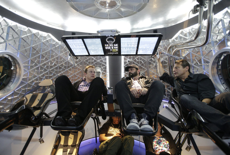 Photo -  Elon Musk, left, CEO and CTO of SpaceX, mingles with invited guests Thursday inside the SpaceX  Dragon V2 spaceship at the headquarters  in Hawthorne, Calif.    Jae C. Hong -  AP