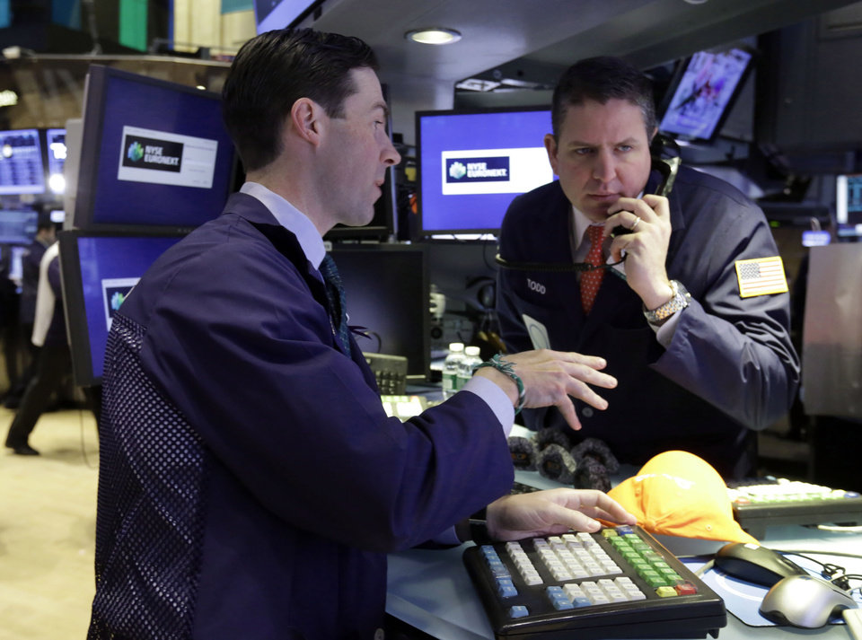 Specialists John McNierney, left, and Todd Abrahall work on the floor of the New York Stock Exchange Tuesday, Jan. 22, 2013. Stocks are wavering in early trading on Wall Street as U.S. companies turn in a mixed batch of earnings reports. (AP Photo/Richard Drew)
