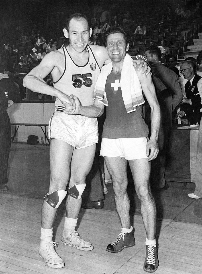 Photo - Jesse Renick, left, captain of the U.S. men's Olympic basketball team, from Bartlesville, Okla., is congratulated by Swiss team captain Maurice Chollet in Harringay Arena in London, England, July 30, 1948. The U.S. team beat the Swiss team, 86-21. Renick was posthumously inducted into the Oklahoma Sports Hall of Fame on March 20, 2012. (AP Photo)