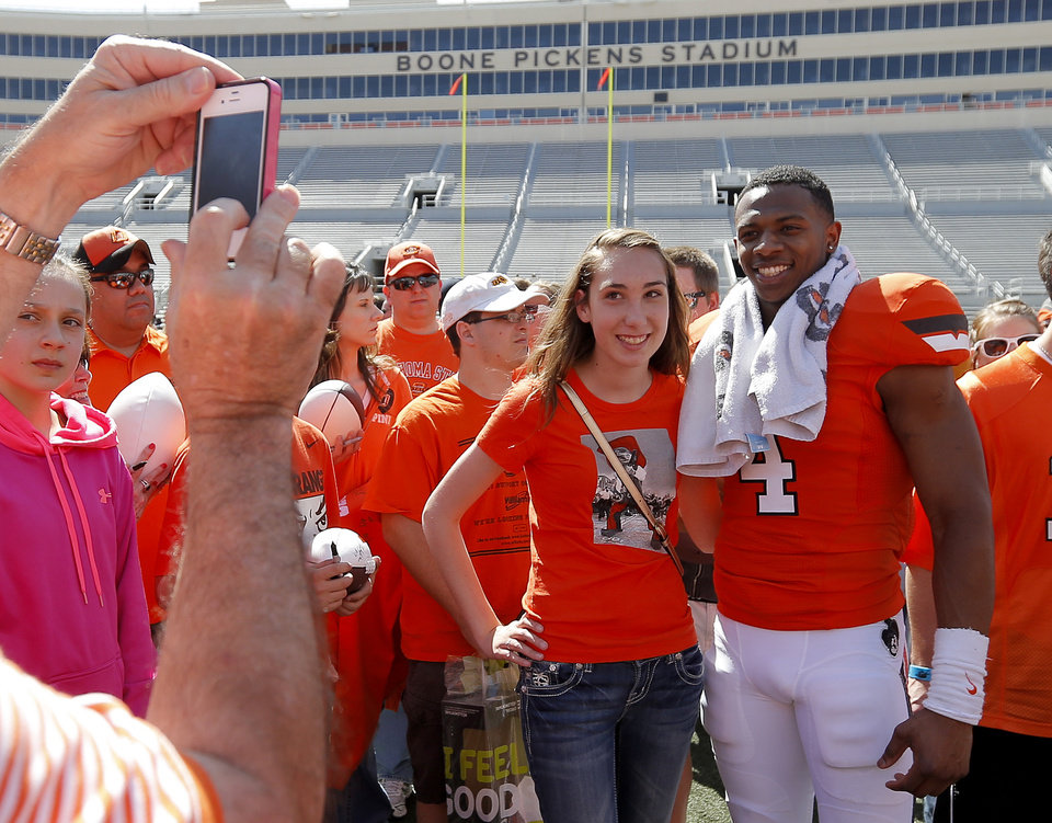 Micah Olson, 15, gets her picture taken with Oklahoma State's Justin Gilber after OSU's spring football game at Boone Pickens Stadium in Stillwater, Okla., Sat., April 20, 2013. Photo by Bryan Terry, The Oklahoman