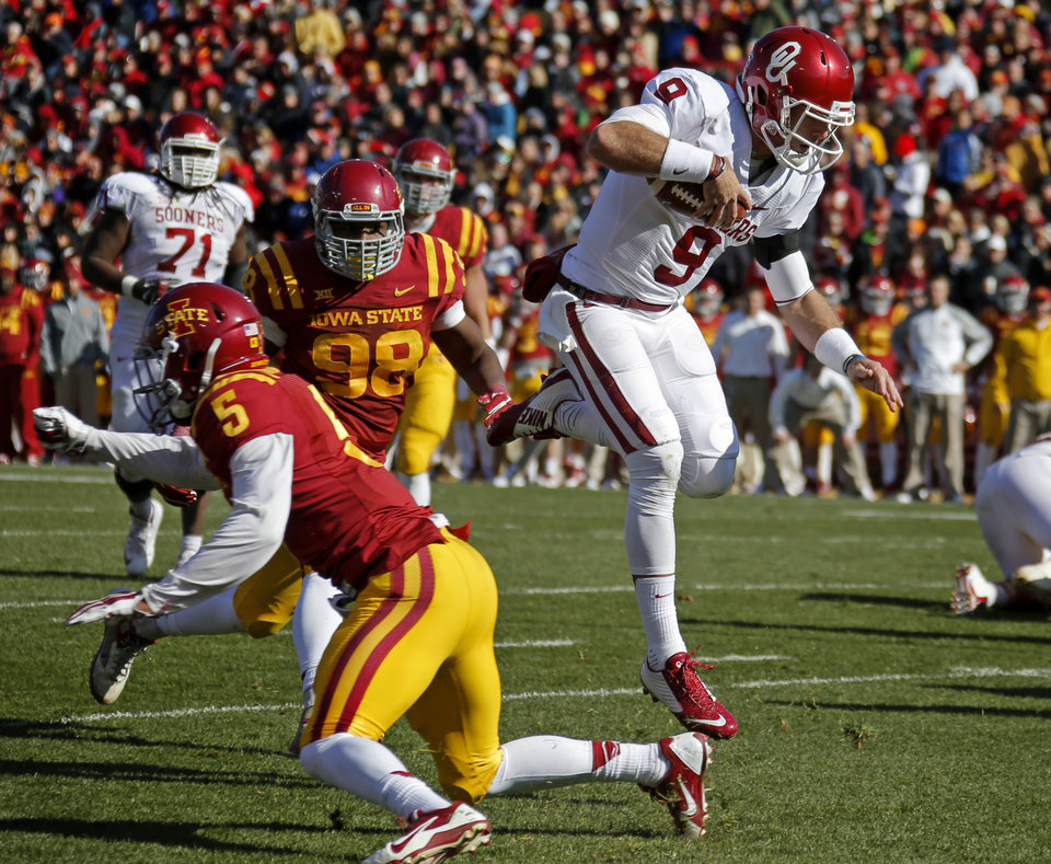 Photo - Oklahoma's Trevor Knight (9) leaps past Iowa State's Kamari Cotton-Moya (5) and Trent Taylor (98) during a college football game between the University of Oklahoma Sooners (OU) and the Iowa State Cyclones (ISU) at Jack Trice Stadium in Ames, Iowa, Saturday, Nov. 1, 2014. Photo by Bryan Terry, The Oklahoman