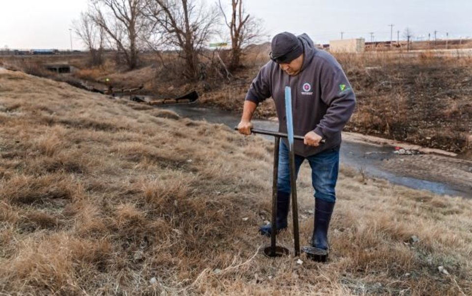 Photo -  City of Oklahoma City Field Supervisor Steven Wright uses a valve key to start the flow of water to drain the mile-long Bricktown Canal in Oklahoma City, Okla Tuesday, Jan. 21, 2020. The canal holds 3 million gallons of water, and will take up to two weeks to clean out the silt and debris.   [Chris Landsberger/The Oklahoman]