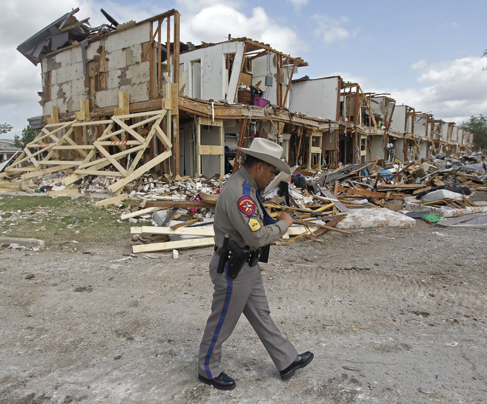 Photo - Texas Department of Public Safety Sgt. Jason Reyes walks past a damaged apartment complex, Sunday, April 21, 2013, four days after an explosion at a fertilizer plant in West, Texas. The massive explosion at the West Fertilizer Co. Wednesday night killed 14 people and injured more than 160. (AP Photo/The Dallas Morning News, Michael Ainsworth, Pool)