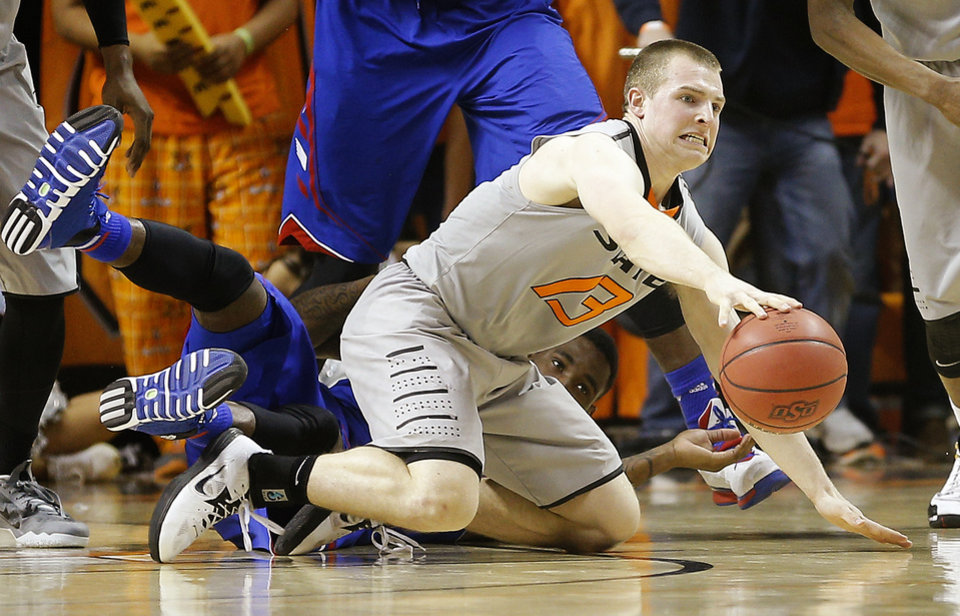 Photo - Oklahoma State's Phil Forte (13) gains control of a loose ball in front of Kansas' Jamari Traylor (31) during an NCAA college basketball game between Oklahoma State University (OSU) and the University of Kansas at Gallagher-Iba Arena in Stillwater, Okla., Saturday, March 1, 2014. Oklahoma State won 72-65. Photo by Bryan Terry, The Oklahoman