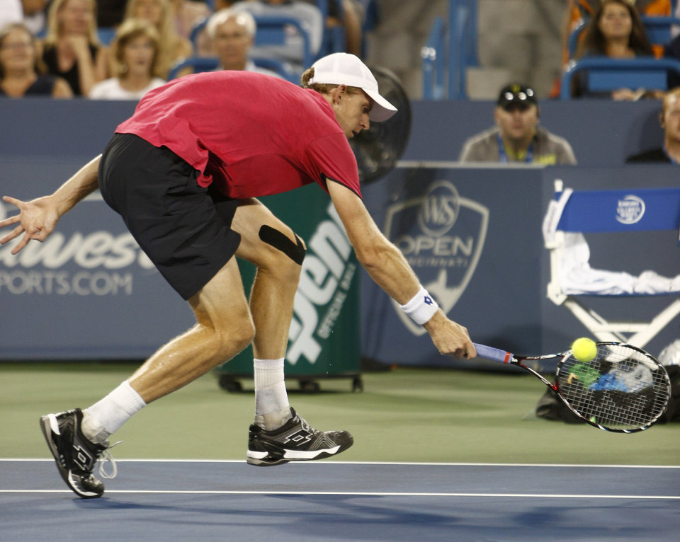Photo - Kevin Anderson, from South Africa, reaches for a volley from John Isner, from the United States, in a first round match at the Western & Southern Open tennis tournament, Monday, Aug. 11, 2014, in Mason, Ohio. Isner won 6-3, 6-4. (AP Photo/David Kohl)