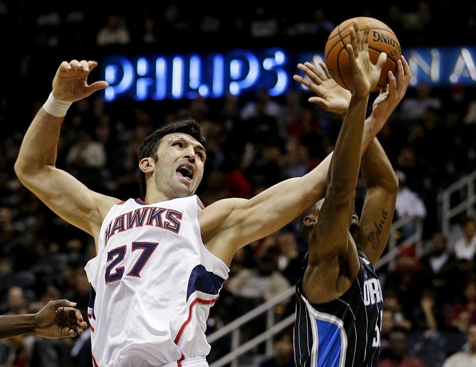 Atlanta Hawks\' Zaza Pachulia (27), of the Republic of Georgia, grabs a rebound from Orlando Magic\'s E\'Twaun Moore in the second quarter of an NBA basketball game, Monday, Nov. 19, 2012, in Atlanta. (AP Photo/David Goldman)