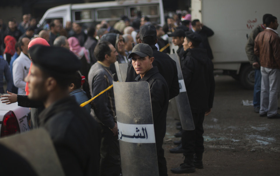 Photo - Egyptian police guard the Imbaba courthouse after an explosion damaged the building despite a massive security operation to protect polling stations and voters, in Cairo, Egypt, Tuesday, Jan. 14, 2014. No one was reported injured in the blast. Egyptians have started voting on a draft for their country's new constitution that represents a key milestone in a military-backed roadmap put in place after President Mohammed Morsi was overthrown in a popularly backed coup last July. (AP Photo/Khalil Hamra)