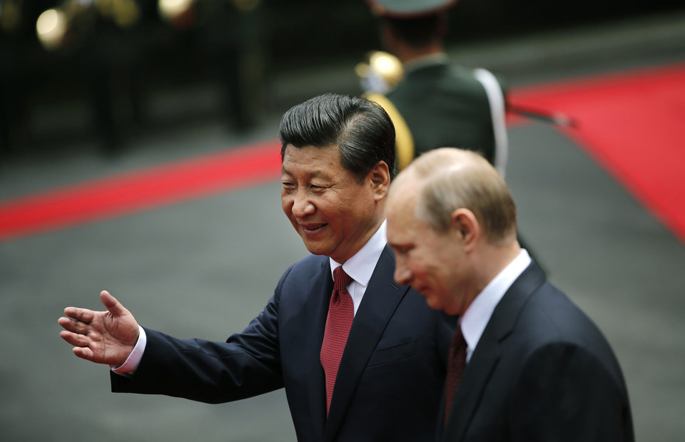 Photo - Russia's President Vladimir Putin, right, and China's President Xi Jinping review an honor guard during a welcome ceremony at the Xijiao State Guesthouse ahead of the fourth Conference on Interaction and Confidence Building Measures in Asia (CICA) summit, in Shanghai, China, Tuesday, May 20, 2014. (AP Photo/Carlos Barria, Pool)