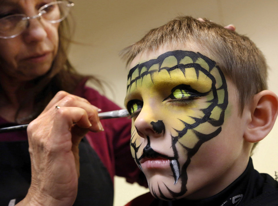 "Austin Collins, 5, a kindergarten student at Santa Fe Elementary School in Moore, selected a ""snake eyes"" design for ""Mona Lisa"" artist Lisa Powers to paint on his face.  Residents of Moore were invited to celebrate the Mexican tradition of honoring deceased loved ones at the Moore Public Library's Day of the Dead Culture Festival on  Saturday, Oct. 27, 2012. Activities included Day of the Dead bread and merengue bones prepared by Platt College students and staff, musical performances, face painting, storytelling and crafts.  Photo by Jim Beckel, The Oklahoman"