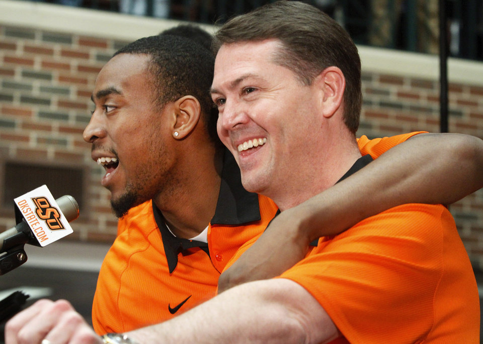 Photo - OSU mens basketball coach Travis Ford smiles as player  Markel Brown, currently a junior, puts his arm around the coach when he came to the microphone. OSU basketball players Le'Bryan Nash, Markel Brown and Marcus Smart delighted  fans when they announced at a noontime press conference they intend to return for another season as members of the Cowboys basketball team. Cheering fans lined all levels in the Student Union atrium Wednesday, April 17, 2013.    by Jim Beckel, The Oklahoman.