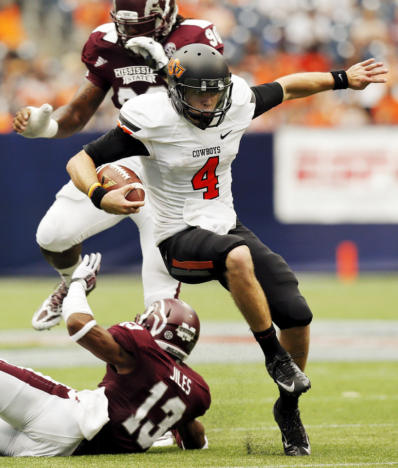 Oklahoma State's J.W. Walsh (4) avoids Mississippi State's Cedric Jiles (13) and Denico Autry (90) on a quarterback keeper during the AdvoCare Texas Kickoff college football game between the Oklahoma State University Cowboys (OSU) and the Mississippi State University Bulldogs (MSU) at Reliant Stadium in Houston, Saturday, Aug. 31, 2013. OSU won, 21-3. Photo by Nate Billings, The Oklahoman