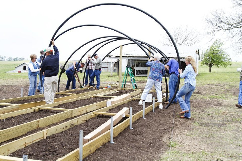 Participants at a previous workshop use tubing to construct a hoop house frame.  Photo provided