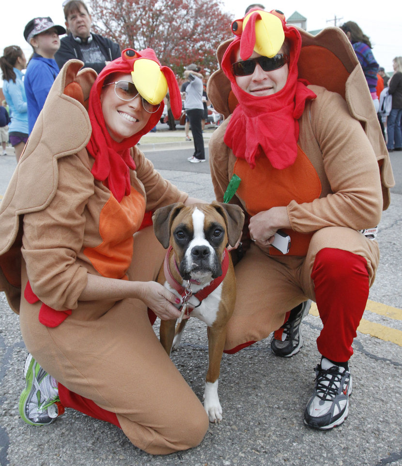 Left: Ashley and Jeff Buterbaugh wait for the start of the Turkey Trot on Thursday with their dog Miley in Edmond. The annual Turkey Trot is a fundraiser for Turning Point Ministries. Photos by Steve Gooch, The Oklahoman