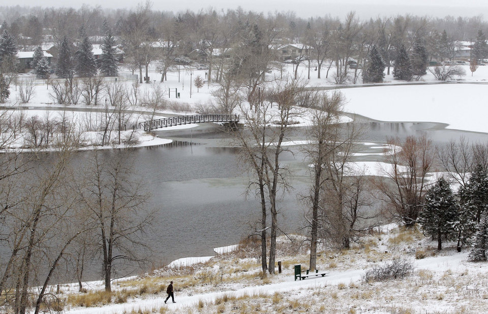 Photo - A man walks alongside a lake in Boulder, Colo., Wednesday Dec. 19, 2012. A storm that has dumped more than a foot of snow in the Rocky Mountains is heading east and is forecast to bring the first major winter storm of the season to the central plains and Midwest. (AP Photo/Brennan Linsley)