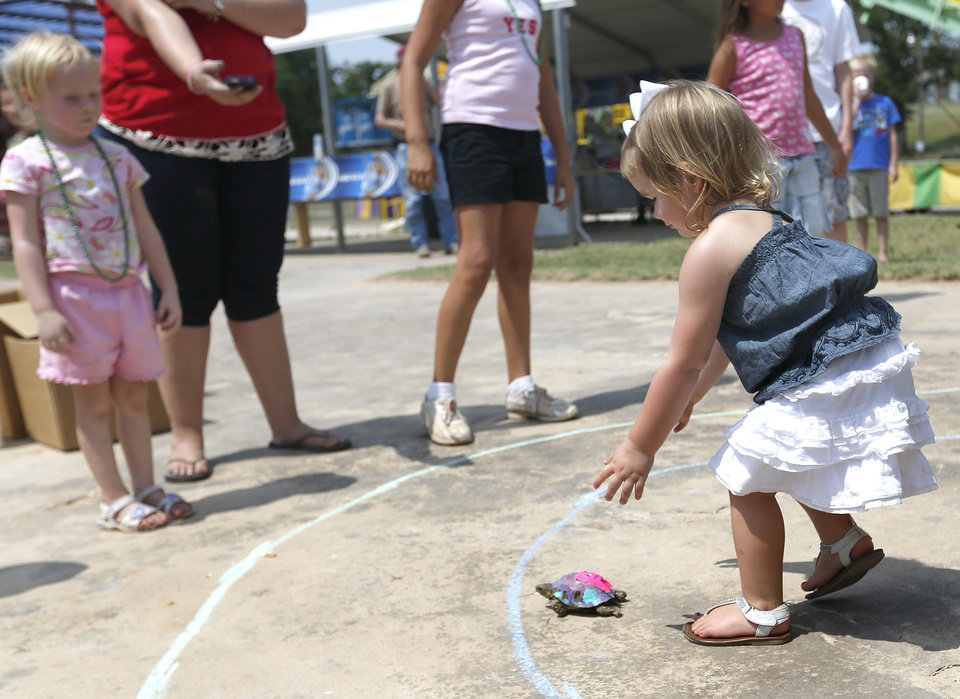 Photo - Mia Holmes, 2, follows her turtle during a turtle race Saturday at the Blackberry Festival in McLoud.