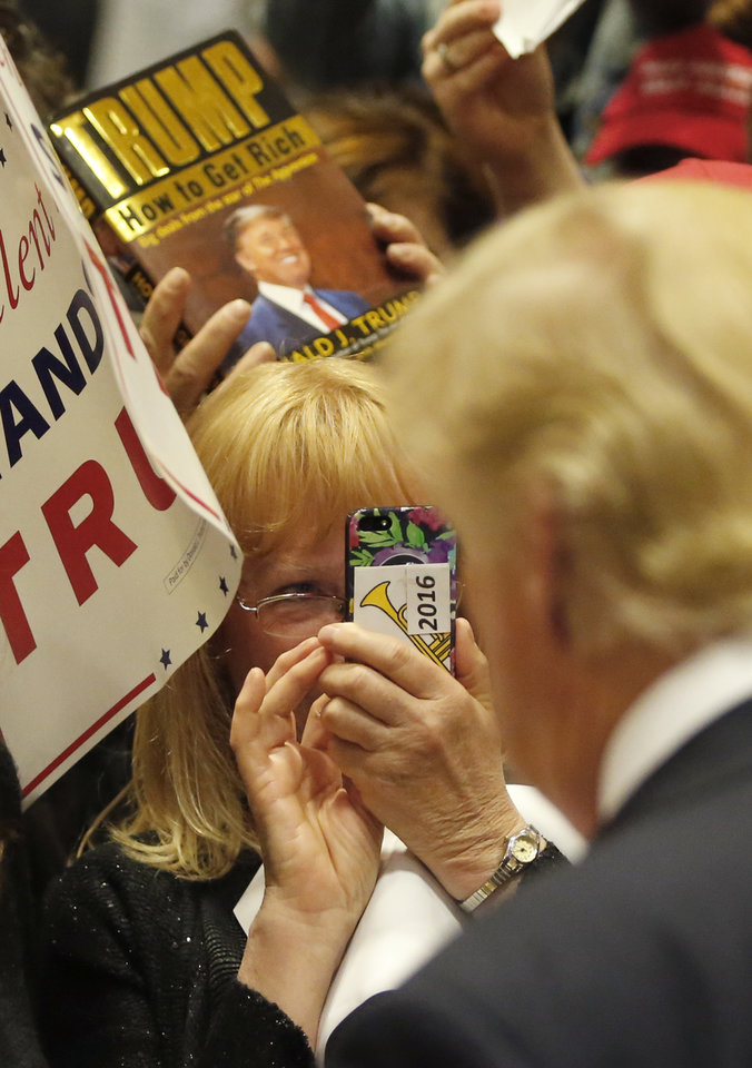 Photo - A supporter of Republican presidential candidate, Donald Trump, takes his photograph after a rally at Nathan Hale High School, Sunday, April 3, 2016, in West Allis, Wis. (AP Photo/Charles Rex Arbogast)