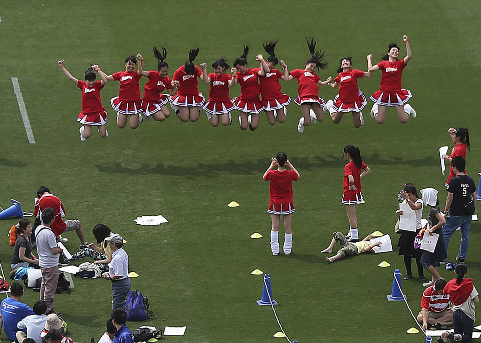 The volunteers jump to take a photo on the pitch during an event at the National Stadium in Tokyo, Sunday, May 25, 2014. Tokyo\'s National Stadium, the centerpiece of the 1964 Summer Olympics, hosted its final sporting event on Sunday before it will be demolished to make way for a new 80,000-seat structure that will be the main venue of the 2020 Olympics. (AP Photo/Eugene Hoshiko)