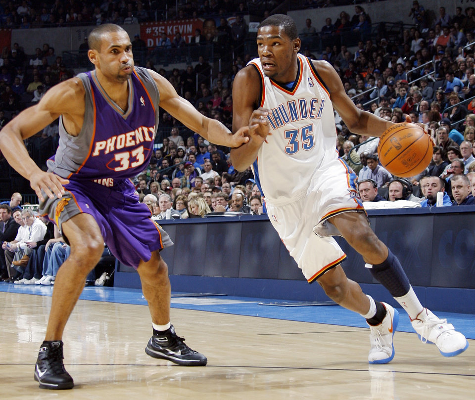 Photo - Oklahoma City's Kevin Durant (35) drives the ball as Grant Hill (33) of Phoenix defends during the NBA basketball game between the Phoenix Suns and the Oklahoma City Thunder at the Ford Center in Oklahoma City, Tuesday, Feb. 23, 2010. Photo by Nate Billings, The Oklahoman ORG XMIT: KOD