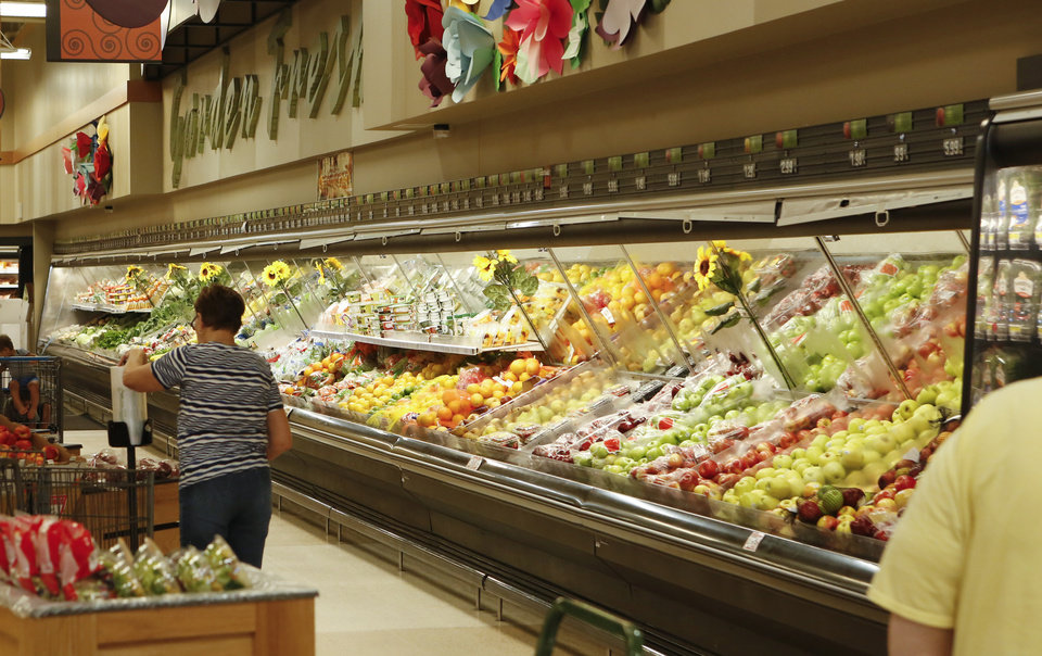 Photo -  People shop in the produce section at the Commissary at Tinker Air Force Base. [Photo by Jacob Derichsweiler, The Oklahoman]
