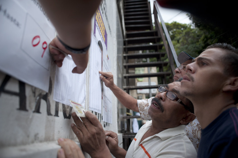 Residents look for their names as at a polling station to vote for presidential elections at the Petare neighborhood in Caracas, Venezuela, Sunday, Oct. 7, 2012. President Hugo Chavez is running against opposition candidate Henrique Capriles.(AP Photo/Sharon Steinmann)