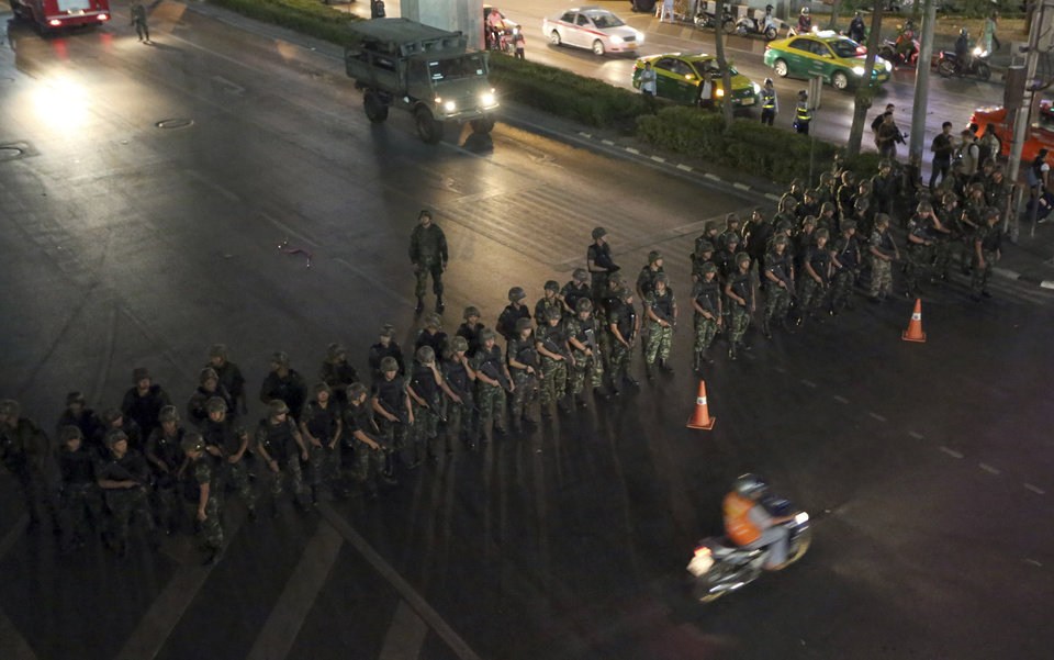 Photo - A motorcyclist rides past Thai soldiers blocking the road to prevent activists and pro-government protesters from gathering to protest against the coup in downtown Bangkok, Thailand Friday, May 23, 2014. Ousted members of Thailand's former government turned themselves in to the country's new military junta Friday, as soldiers forcefully dispersed hundreds of anti-coup activists who defied a ban on large-scale gatherings to protest the army's seizure of power. (AP Photo/Apichart Weerawong)