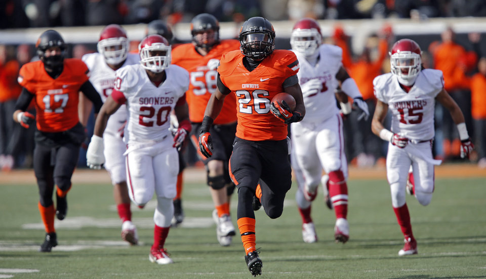 Photo - Oklahoma State's Desmond Roland (26) runs for a touchdown on the first play from scrimmage that was called back due to a penalty during the Bedlam college football game between the Oklahoma State University Cowboys (OSU) and the University of Oklahoma Sooners (OU) at Boone Pickens Stadium in Stillwater, Okla., Saturday, Dec. 7, 2013. Photo by Chris Landsberger, The Oklahoman