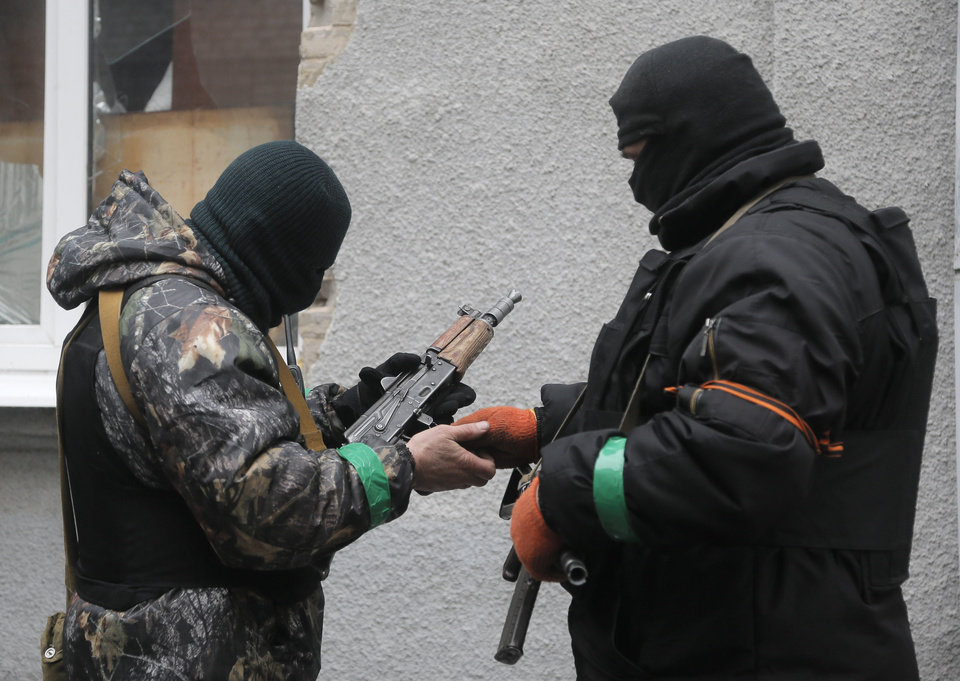 Photo - Pro-Russian gunmen check their weapons at a seized police station in the eastern Ukraine town of Slovyansk on Sunday, April 13, 2014. Pro-Moscow protesters have seized a number of government buildings in the east over the past week, undermining the authority of the interim government in the capital, Kiev. (AP Photo/Efrem Lukatsky)