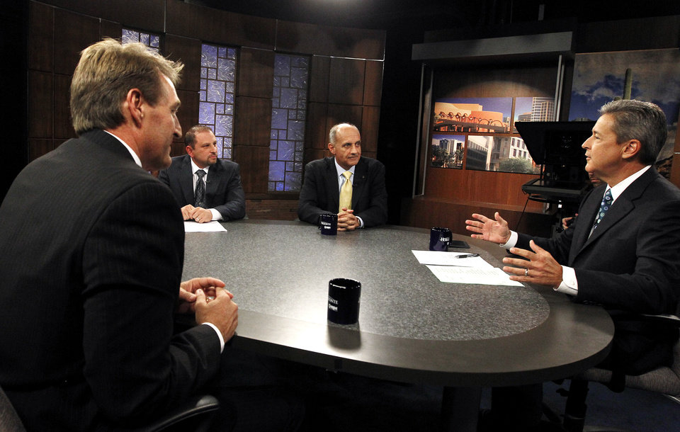 From left to right, Rep. Jeff Flake, R-Ariz., Libertarian candidate Marc Victor, and Democrat Richard Carmona listen to moderator Ted Simons, host and managing editor of Arizona Horizon of Eight, Arizona PBS, give the debate ground rules while in studio prior to an Arizona U.S. Senate debate Wednesday, Oct. 10, 2012, in Phoenix. The two are vying for the seat left open by retiring Sen. Jon Kyl, R-Ariz. (AP Photo/Ross D. Franklin)