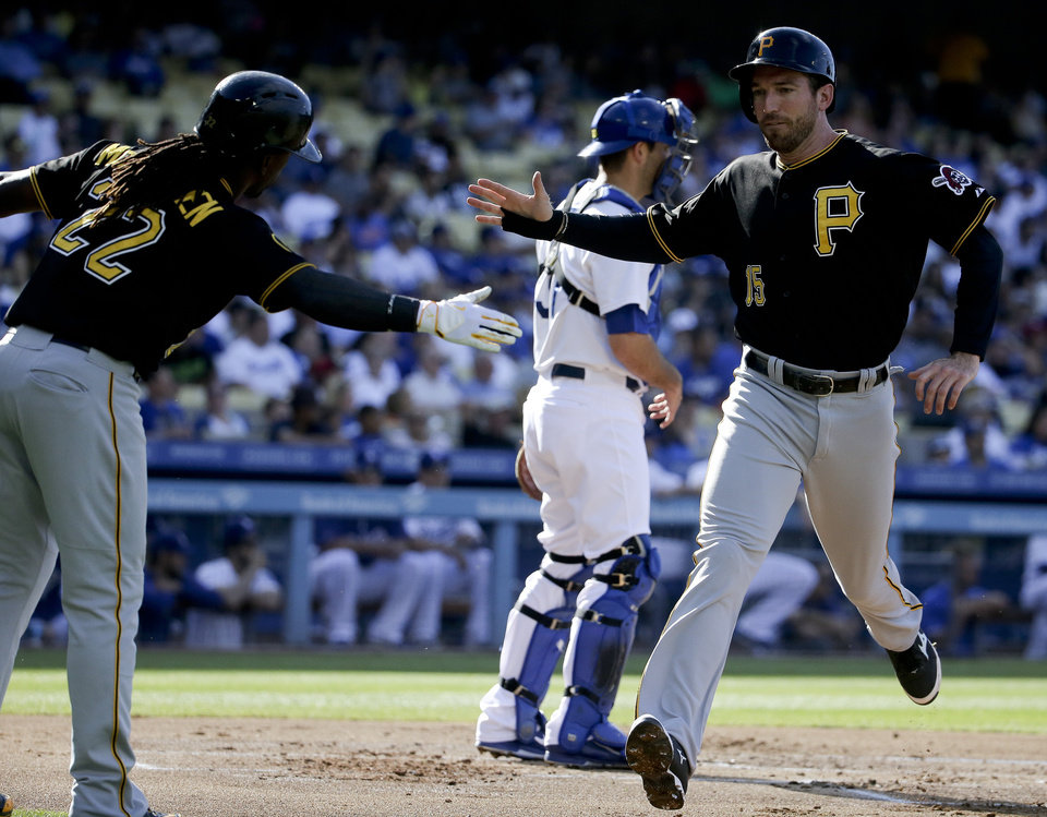 Photo - Pittsburgh Pirates' Ike Davis, right, celebrates past Los Angeles Dodgers catcher Drew Butera with Andrew McCutchen after scoring on a single by Pedro Alvarez during first inning of a baseball in Los Angeles, Sunday, June 1, 2014. (AP Photo/Chris Carlson)