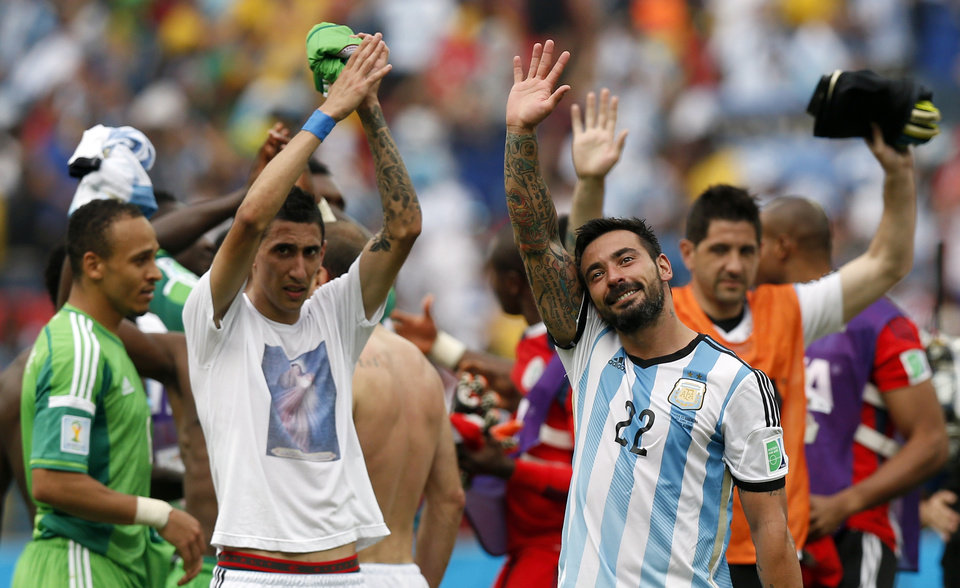 Photo - Argentina's Angel di Maria, left, and Ezequiel Lavezzi wave to spectators after their 3-2 win over Nigeria in the group F World Cup soccer match between Nigeria and Argentina at the Estadio Beira-Rio in Porto Alegre, Brazil, Wednesday, June 25, 2014. (AP Photo/Victor R. Caivano)