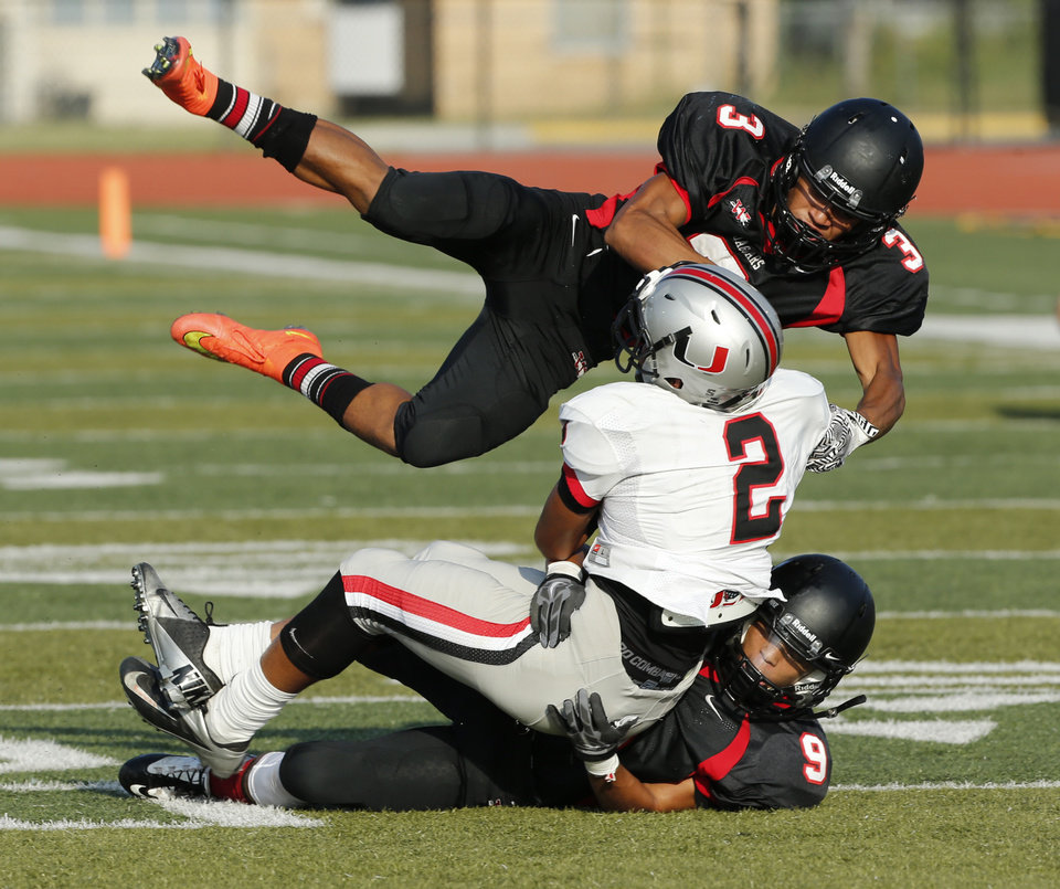 Photo - Cassius Hill, 3, and Mike Hotchkins of Westmoore bring down Tulsa Union's Kameron McQueen during a high school football scrimmage at Harve Collins Field in Norman, Okla., on Thursday, Aug. 21, 2014. Photo by Steve Sisney, The Oklahoman