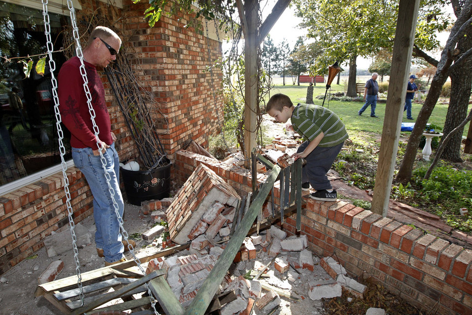 Photo - Jess Burrow, left, and James Patterson, look over the damage caused outside the home of Joe and Mary Reneau when their chimney was toppled by Saturday's earthquake, in Sparks, Okla., Sunday, Nov. 6, 2011. (AP Photo/Sue Ogrocki) ORG XMIT: OKSO108