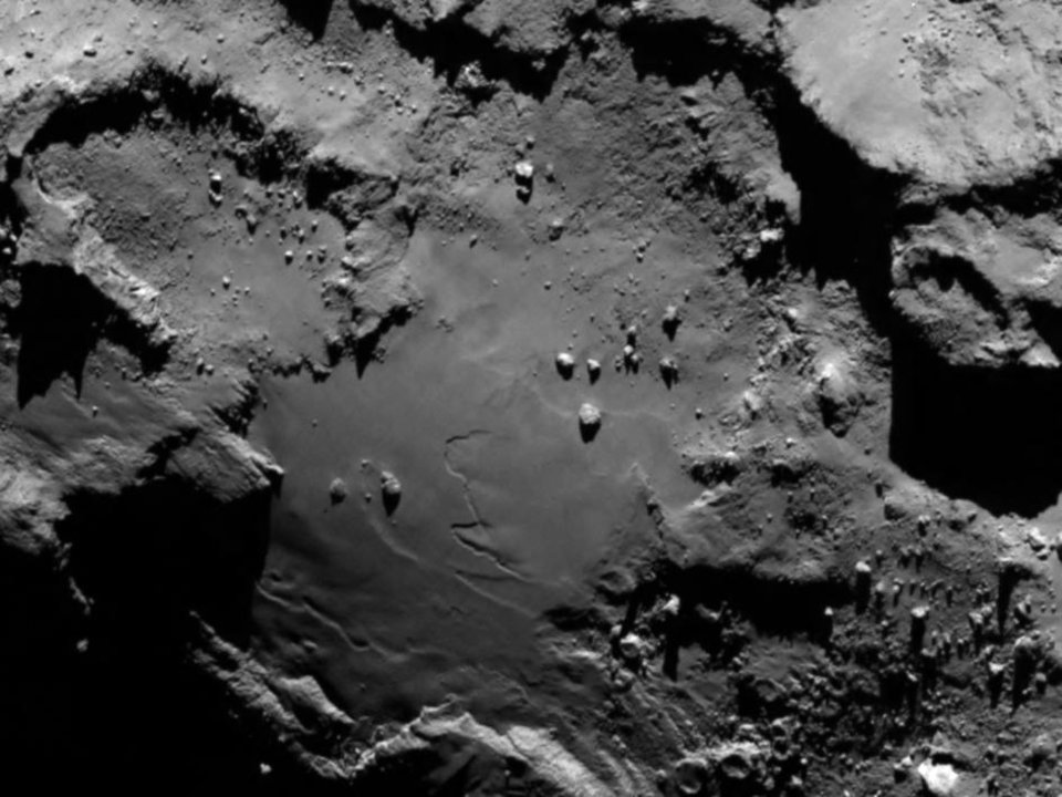 Photo - Close up detail focusing on a smooth region on the 'base' of the 'body' section of comet 67P/Churyumov-Gerasimenko. The image was taken by Rosetta's OSIRIS narrow-angle camera and downloaded Wednesday, Aug. 6, 2014. The image clearly shows a range of features, including boulders, craters and steep cliffs. The image was taken from a distance of 130 km and the image resolution is 2.4 meters per pixel. A mission to land the first space probe on a comet reaches a major milestone when the unmanned Rosetta spacecraft finally catches up with its quarry on Wednesday. It's a hotly anticipated rendezvous: Rosetta flew into space more than a decade ago and had to perform a series of complex maneuvers to gain enough speed to chase down the comet on its orbit around the sun. (AP Photo/ESA/Rosetta/MPS for OSIRIS Team )