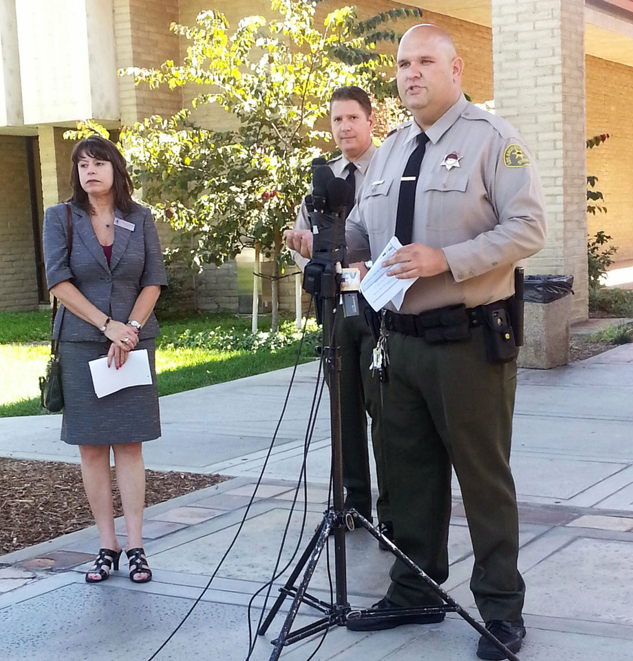 Photo - Santa Clarita Valley Sheriff's Station deputy Joshua Dubin announces the arrest of a 15-year-old boy Sunday, Aug. 17, 2014, on suspicion of posting online threats to shoot students at Southern California schools in Valencia, Calif. Deputies arrested the teen after serving a search warrant at his home, Lt. Tom Bryski said. (AP Photo/The Santa Clarita Valley Signal, Kristine Alfaro)