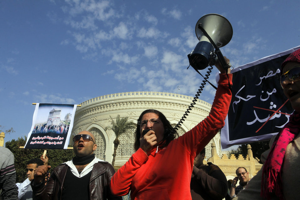 """An Egyptian protester shouts anti--President Mohammed Morsi slogans in front of the presidential palace in Cairo, Egypt, Friday, Jan. 25, 2013. Authorities expect a violent anniversary of the 2011 uprising that toppled long-time authoritarian President Hosni Mubarak. Arabic reads, """"save Egypt from the rule of the brotherhood leader."""" and at left read """"from Assiut train accident to Badrasheen train accident, where are you?""""  (AP Photo/Amr Nabil) ORG XMIT: AMR111"""
