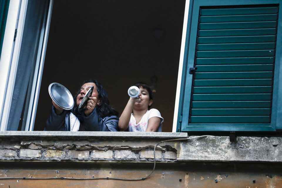 Photo -  A woman and a girl play pots from the window of they home during a flash mob launched throughout Italy to bring people together and try to cope with the emergency of coronavirus, at the Garbatella neighborhood, in Rome, Friday, March 13, 2020. Italians have been experiencing yet further virus-containment restrictions after Premier Giuseppe Conte ordered restaurants, cafes and retail shops closed after imposing a nationwide lockdown on personal movement. For most people, the new coronavirus causes only mild or moderate symptoms. For some it can cause more severe illness. (Cecilia Fabiano/LaPresse via AP)