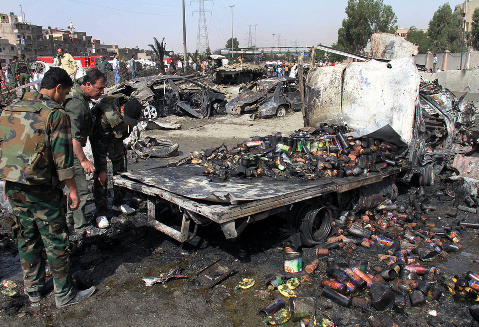 Syrian soldiers check a burned truck in front of a damaged military intelligence building where two bombs exploded, at Qazaz neighborhood in Damascus, Syria, on Thursday May 10, 2012. Two strong explosions ripped through the Syrian capital Thursday, killing or wounding dozens of people and leaving scenes of carnage in the streets in an assault against a center of government power. (AP Photo/Bassem Tellawi) ORG XMIT: BEI122