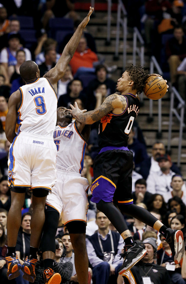 Photo - Phoenix Suns' Michael Beasley (0) has his shot blocked by Oklahoma City Thunder's Kendrick Perkins, center, as Serge Ibaka (9), of the Congo, comes in to defend during the first half in an NBA basketball game, Sunday, Feb. 10, 2013, in Phoenix. (AP Photo/Ross D. Franklin)