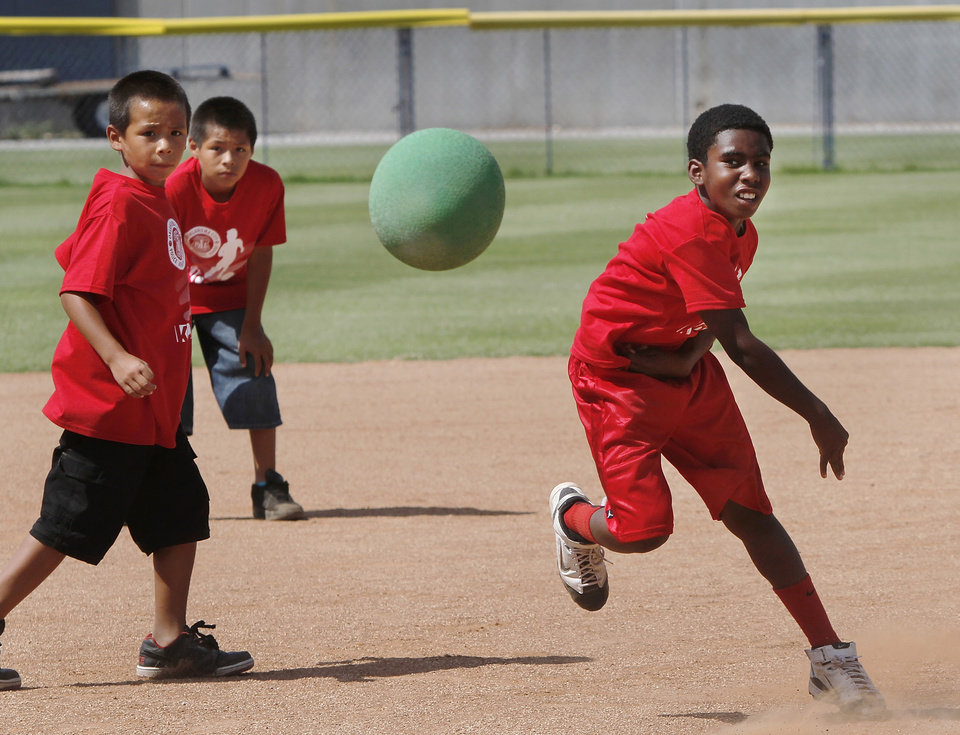 YOUTH KICKBALL TOURNAMENT / CHILD / CHILDREN / KIDS: Two teammates watch the ball as a McKinley Park player aims for a runner from the other team. About 100 youth participated in a kickball tournament at Hall of Fame Stadium Wednesday,  June 26, 2013.   Eight teams represented a variety of recreation centers from different parts of the city. Pilot Center won the tournament which was sponsored by the OKC Parks and Recreation Department in conjunction with the Police Athletic League.  Photo  by Jim Beckel, The Oklahoman.