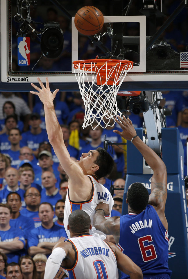 Photo - Oklahoma City's Steven Adams (12) puts up a shot past Los Angeles' DeAndre Jordan (6) during Game 2 of the Western Conference semifinals in the NBA playoffs between the Oklahoma City Thunder and the Los Angeles Clippers at Chesapeake Energy Arena in Oklahoma City, Wednesday, May 7, 2014. Photo by Bryan Terry, The Oklahoman