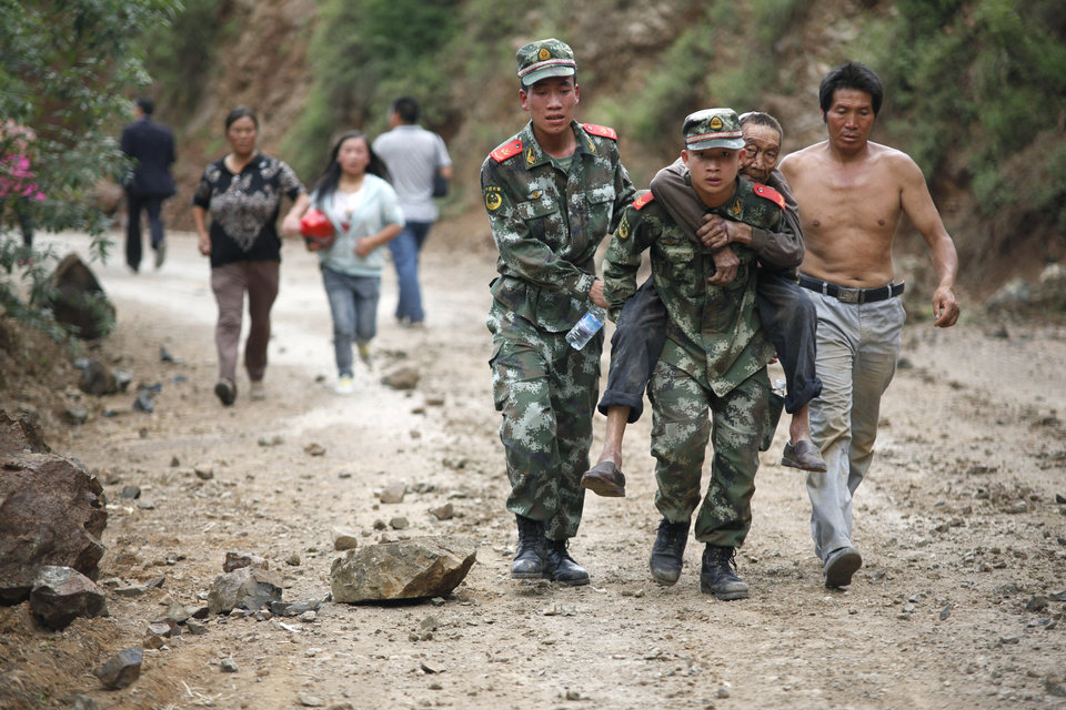 Photo - In this photo released by China's Xinhua News Agency, rescuers transport an injured man after an earthquake in Ludian County of Zhaotong City in southwest China's Yunnan Province, Sunday, Aug. 3, 2014. The magnitude-6.1 quake in southern China's Yunnan province toppled thousands of homes on Sunday, killing scores of people and injuring more than 1,800. (AP Photo/Xinhua, Zhang Guangyu) NO SALES
