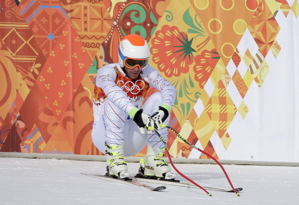 Photo - United States' Bode Miller sits on his skis after finishing the men's downhill at the Sochi 2014 Winter Olympics, Sunday, Feb. 9, 2014, in Krasnaya Polyana, Russia. (AP Photo/Gero Breloer)