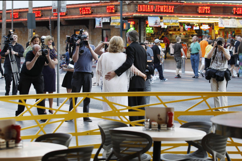 Ames, Iowa residents Nancy Levindowski and Steve Keller have their photo taken and video shot after exchanging wedding vows at the Denny's restaurant on Fremont Street in Las Vegas, Wednesday, April 4, 2013. (AP Photo/Las Vegas Sun, Sam Morris)