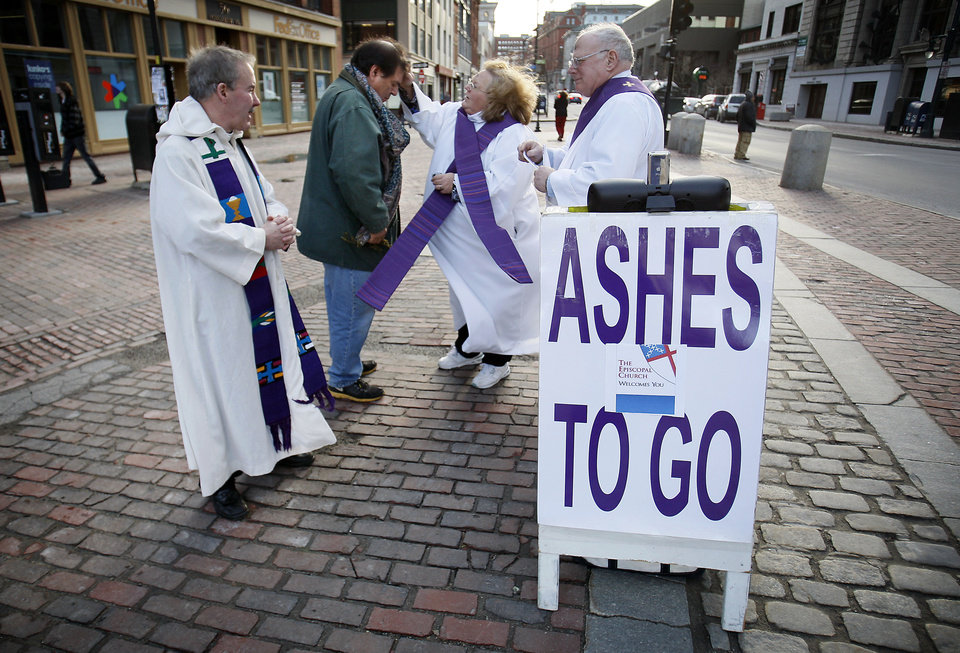 """Jim Alberty receives ashes from Rev. Shirley Bowen on a sidewalk in downtown Portland, Maine, on Ash Wednesday, Feb. 22, 2012. Rev. Tim Higgins, left, and Rev. Peter Bowen look on.  """"You're on the go, so the Epicopal Churches of Southern Maine brings the ashes to you"""" is the church's motto for the holiday. (AP Photo/Robert F. Bukaty)"""